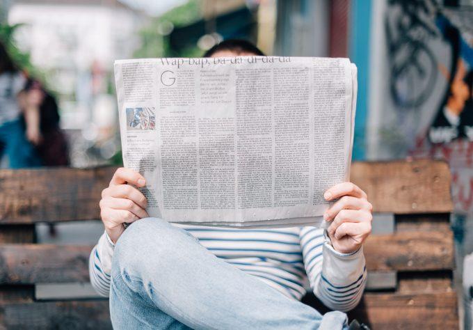 homme lisant son journal sur un banc